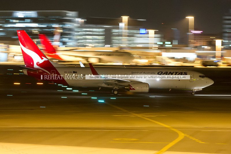 A Qantas Boeing 737-838 at Sydney airport. In the background, the motion blurred silhouette of the Qantas Freight Boeing 767-381F can be seen.