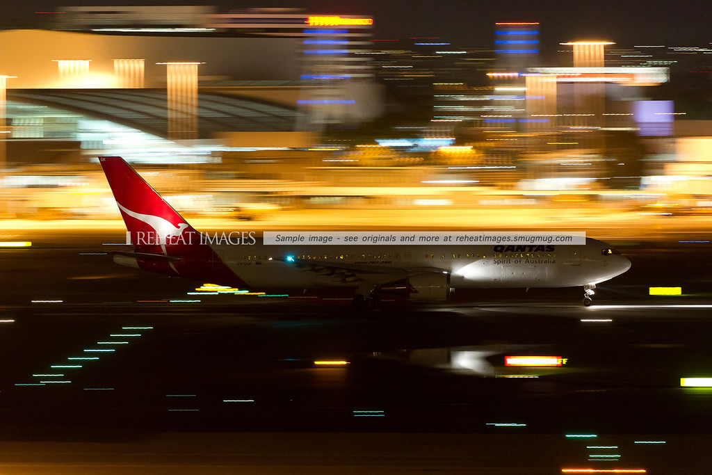 A Qantas Boeing 767-338/ER VH-OGK departs Sydney airport on runway 16 right at night. The lights of the domestic terminal are heavily motion blurred by the low shutter speed.