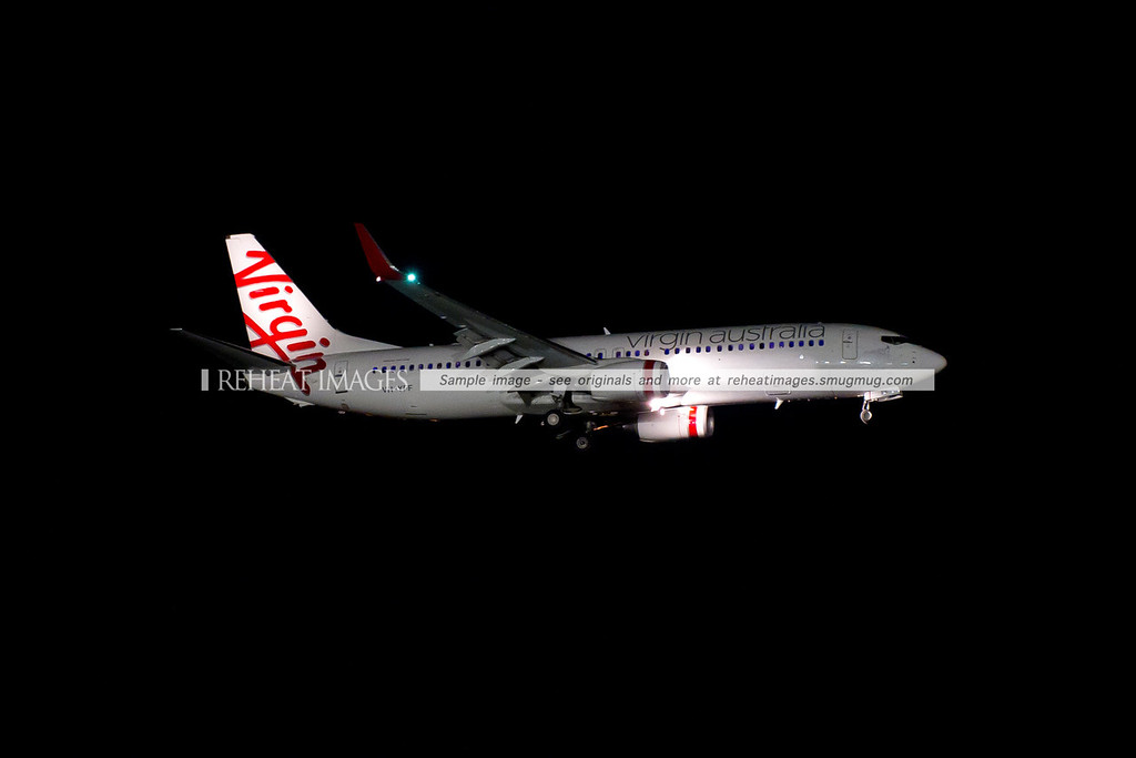 A Virgin Australia Boeing 737-800 approaches Sydney airport at night.