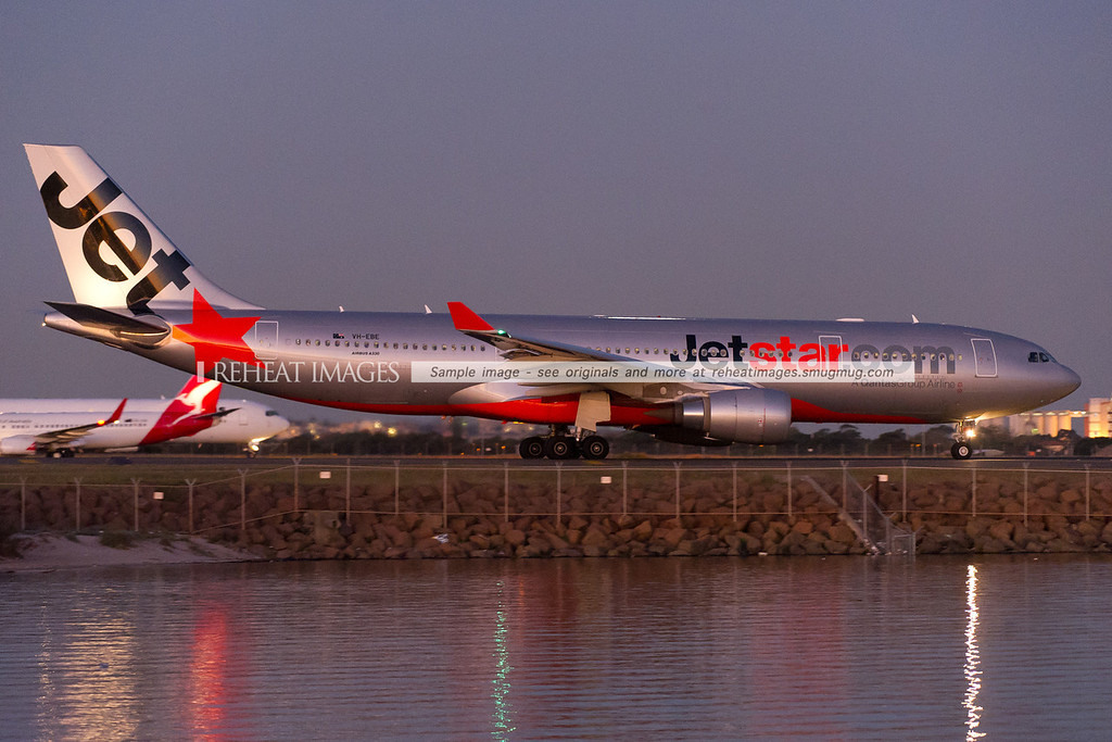 Jetstar's A330-200 VH-EBE is taxiing out to runway 34 left for takeoff at dusk, its lights are reflecting on the water.