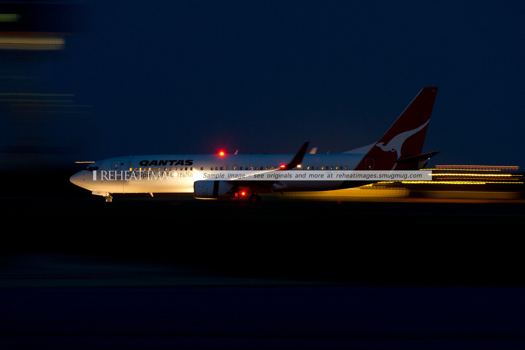 A Qantas Boeing 737-838 arrives at Sydney airport at night.