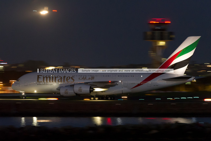 Emirates A380-861 in Sydney at night with another plane seen landing on runway 25 in the background.