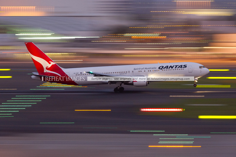 A Qantas Boeing 767-338/ER VH-OGP arrives in Sydney at dusk. A shutter speed of 1/6sec gives the extreme blurring of the foreground and background lights.