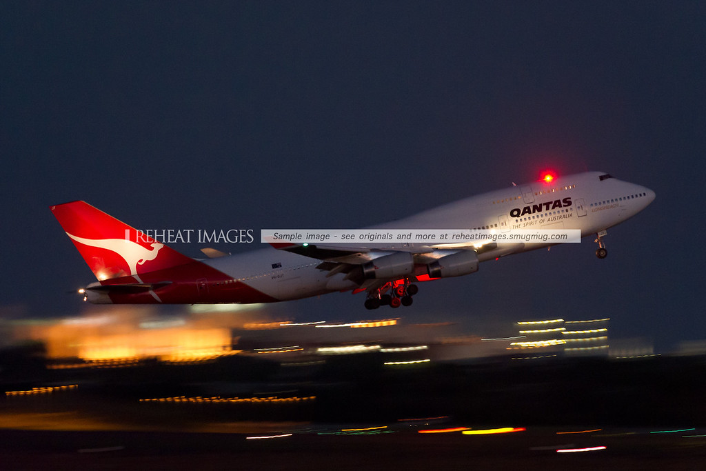 "VH-OJT, A Qantas Boeing 747-438 is leaving Sydney as QF6021, headed to Guangzhou where it will be repainted into the current Qantas colour scheme. The plane still has old ""The Spirit of Australia"" and ""Longreach"" titles."