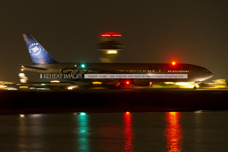 Korean Airlines SkyTeam logo-jet leaves Sydney under the cover of darkness.