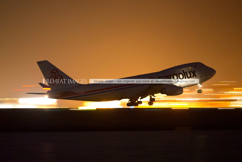 Cargolux LX-MCV B747-400F leaves Sydney at night, silhouetted against the lights of Port Botany.