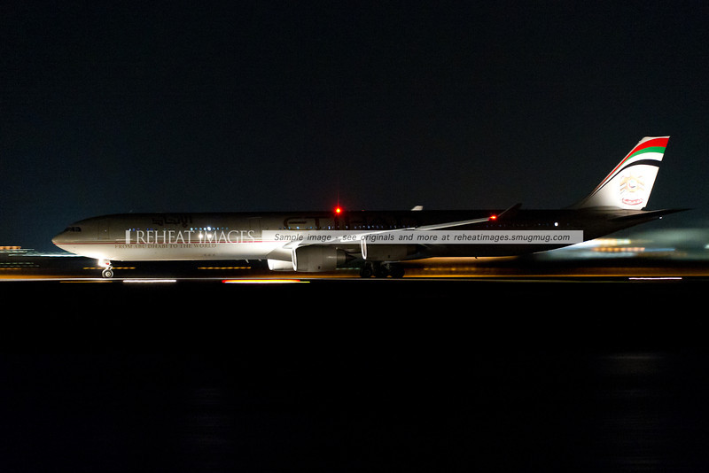 Etihad A340-642 lands at night.
