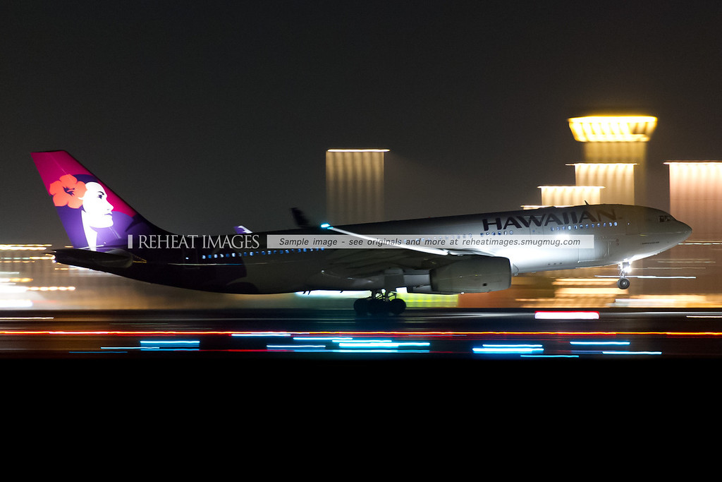 Hawaiian Airbus A330 takes off from Sydney airport at night. The high speed of the plane and the low shutter speed totally blur out any other details. The shot was taken hand-held.