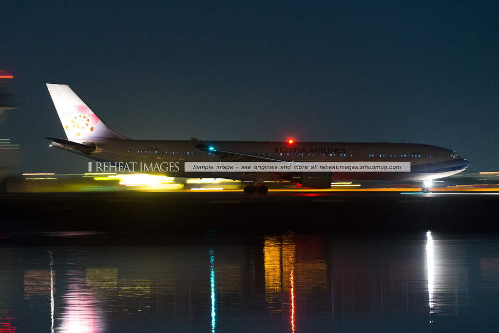 China Airlines A330 Airbus heads for the runway at Sydney airport at 10:10pm at night. The calm water was illuminated by the full moon, the plane lights and other nearby lights. The brightness was due to half second shutter speed and ISO5000 with F/4.0 aperture. A Nikon D800e was used for this photo - my first go with this new Nikon. On first impressions, it is capable of staggering results in low light if used correctly. ISO8000 is quite noisy on this camera, so ISO6400 or less must be used, with a resulting lower shutter speed, or alternatively, use a large aperture lens.