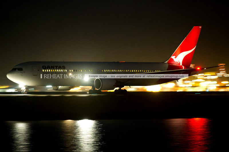 A Qantas Boeing 767-338/ER VH-OGU at Sydney airport, taxiing under the cover of darkness.