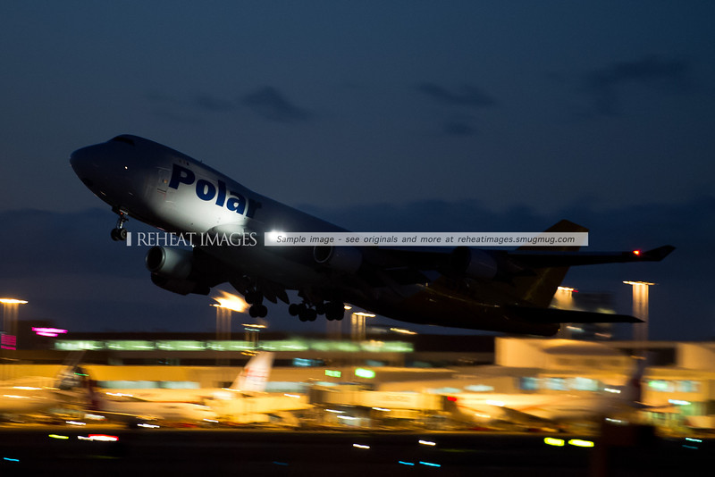 Polar Air B747-400F in the DHL hybrid colour scheme departs Sydney airport at night with the international terminal in the background.