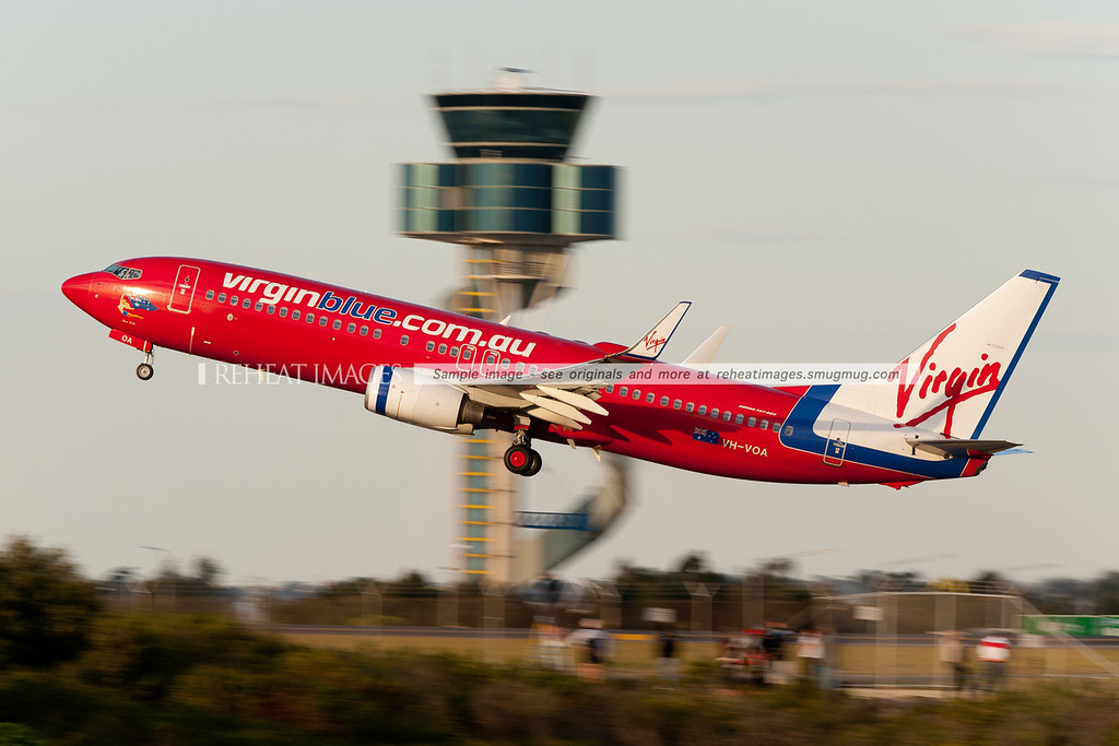 A Virgin Blue Boeing 737-800 takes off from Sydney airport, with the air traffic control tower in the background, and plane-spotters in the foreground.