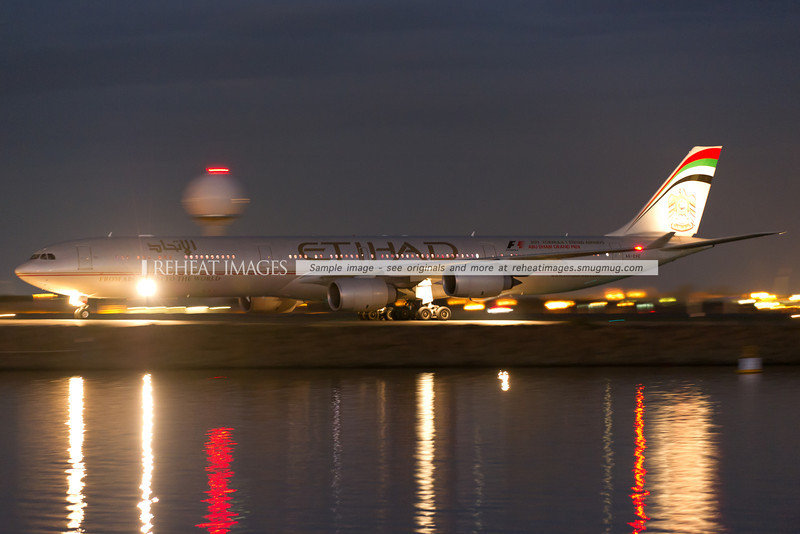 Etihad A340-642 arrives at Sydney airport at night. The water reflects the lights and tail of the plane.