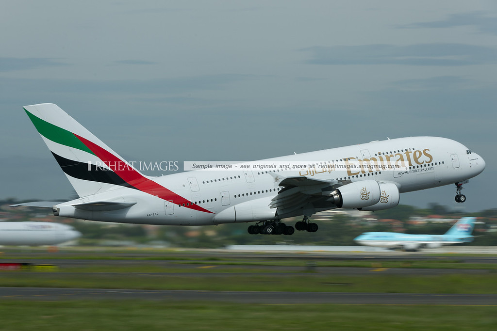 "Emirates A380 departs Sydney airport, while Korean Air B747-400 ""The British Museum"" is taxiing out to the runway in the background."