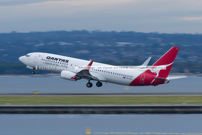 "A Qantas B737-800 ""Cooper Pedy"" takes off from Sydney airport with Botany Bay in the background. The foreground and background are blurred by low shutter speed."