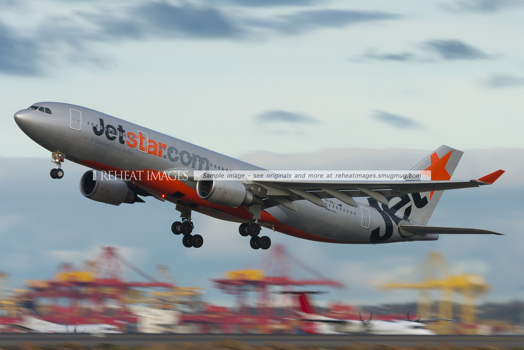A Jetstar Airbus A330 takes off from runway 34 left at  Sydney airport. Dash-8 and SAAB 340 aircraft can be seen waiting in the background.