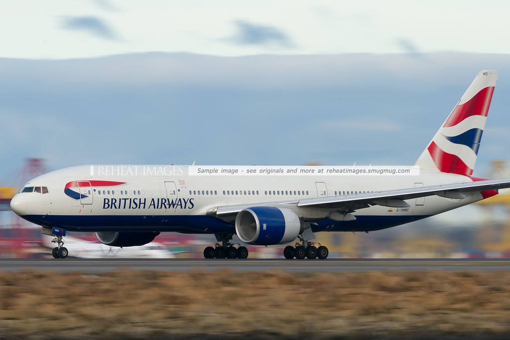 British Airways B777-236/ER takes off from Sydney airport. This particular plane is still wearing plain coloured thrust-reverse cowling on the left engine.