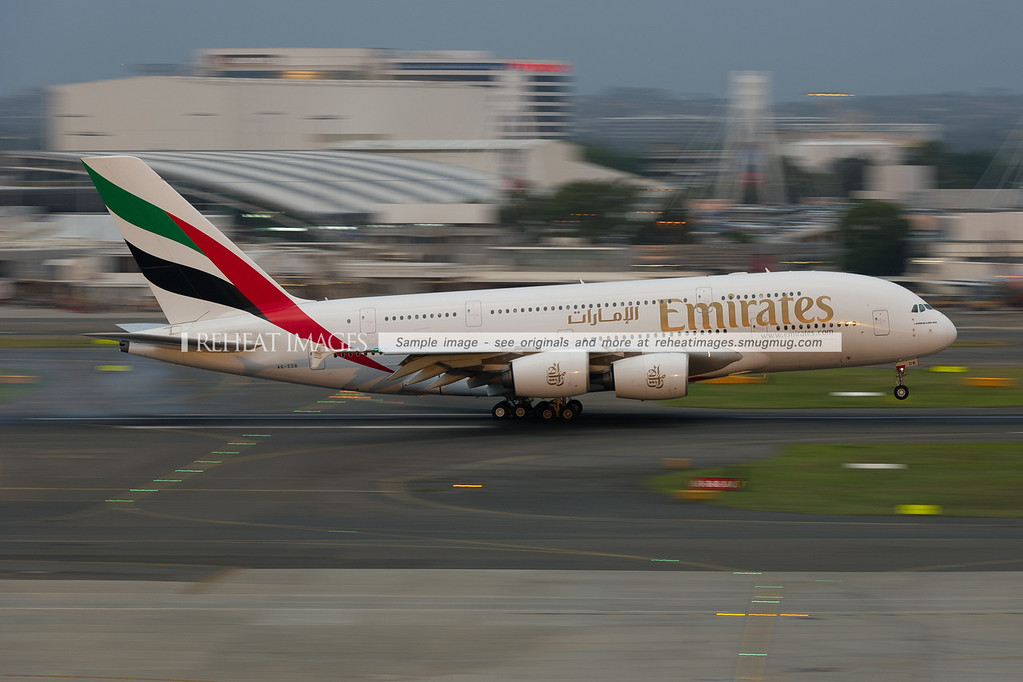 Emirates second Airbus A380-861 arrives in Sydney airport at dusk, lit but soft sunlight peeking through the heavy clouds.