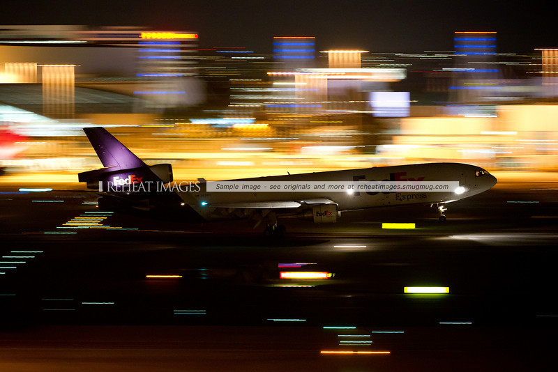 A Fedex McDonnell Douglas MD-11F arrives at Sydney airport on runway 16 right, under the cover of darkness. The crew of the plane are clearly visible through the large flight-deck windows, against the background of the blurred domestic terminal buildings and lights.