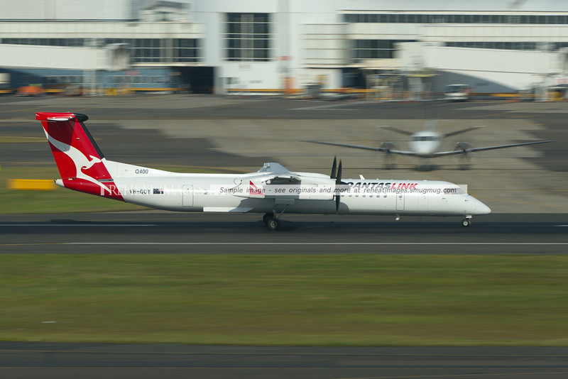 A QantasLink Bombardier Dash 8 Q400 takes off from Sydney airport in front of a Regional Express SAAB 340.