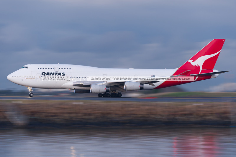 Qantas B747-438 takes off from Sydney airport. The background and foreground are blurred by the low shutter speed.