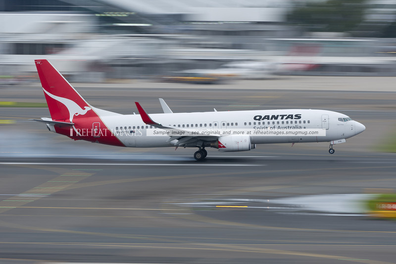 A Qantas B737-838 lands at Sydney airport. The background is blurred by low shutter speed.