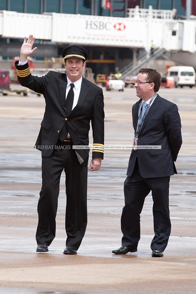A waving John Travolta and Qantas' Alan Joyce at the Qantas 90th anniversary celebrations in Sydney.