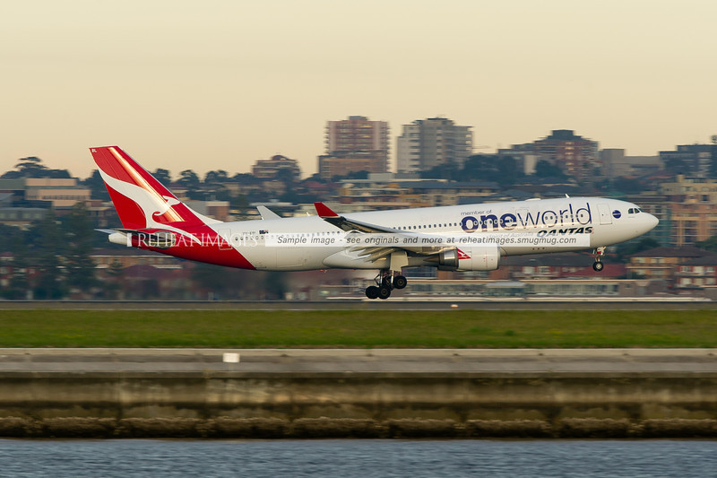 A Qantas Airbus A330-202 lands on runway 34 left at Sydney airport. This plane carries the OneWorld colour scheme.