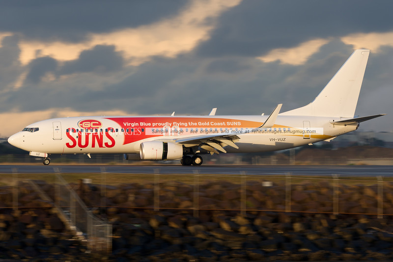 Virgin Blue B737-800 has landed at Sydney airport. It is wearing a promotional colour scheme for the Gold Coast Suns AFL team.