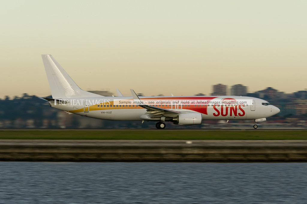 A Virgin Blue Boeing 737-800 takes off from runway 34 right at Sydney airport. This plane carries a special colour scheme promoting the Gold Coast Suns AFL team.
