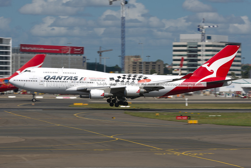 This Qantas 747-48E wears a promotional colour scheme for the F1 Qantas Australian Grand Prix 2011. It is just about to touch down on runway 16 right. In the background, its sibling Wunala Dreaming can be seen at the left of picture.