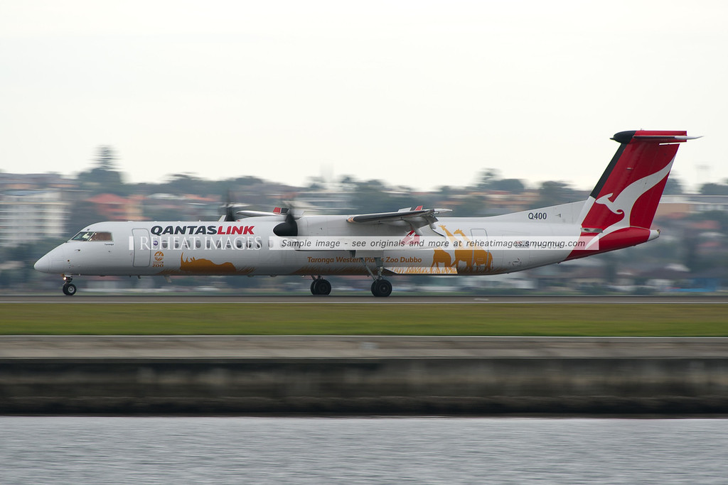 "QantasLink Bombardier Dash-8 Q400 at Sydney airport. This plane is named ""Taronga"", after the Taronga Western Plans Zoo Dubbo, which is advertised on the special colour scheme worn by this plane. Low shutter speed is used here to blur the props and the background."
