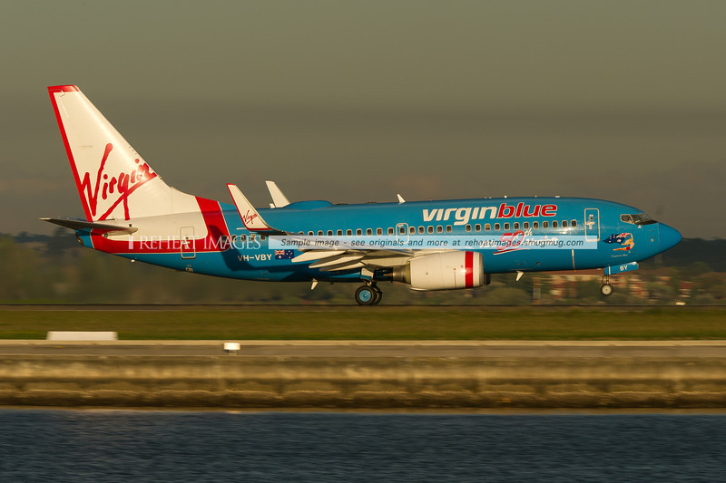 "A Virgin-Blue Boeing 737-700 departs Sydney airport on runway 34 right. In the background is Brighton-Le-Sands. This plane wears a special celebratory colour scheme indicating it was Virgin Blue's 50th B737 aircraft. It is named ""Virginia Blue""."