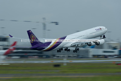 A Thai Airbus A340 takes off from Sydney airport during a brief and light rain shower. Vortices can be seen streaming from the winglets like ribbons, while similar effects can be seen over the top of the wings.