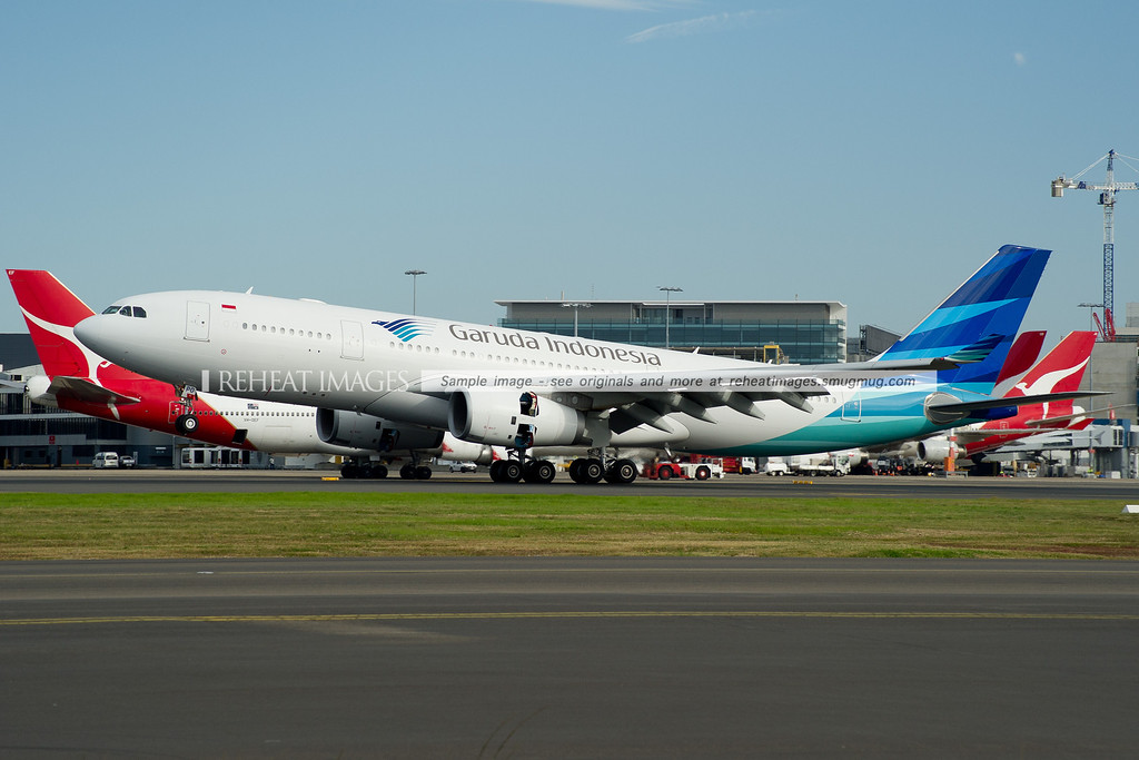 A Garuda Indonesia Airbus A330-200 lands at Sydney Airport on runway 16 right. It passes by numerous Qantas planes.