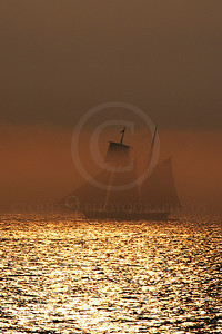 CSS 00003 A two mast civilian sailing ship sails in a golden mist in New York harbor, by John G Lomba