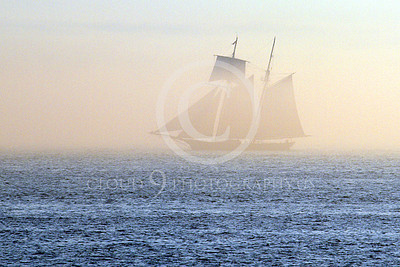 CSS 00002 A two mast civilian sailing ship sails in a golden mist in New York harbor, by John G Lomba