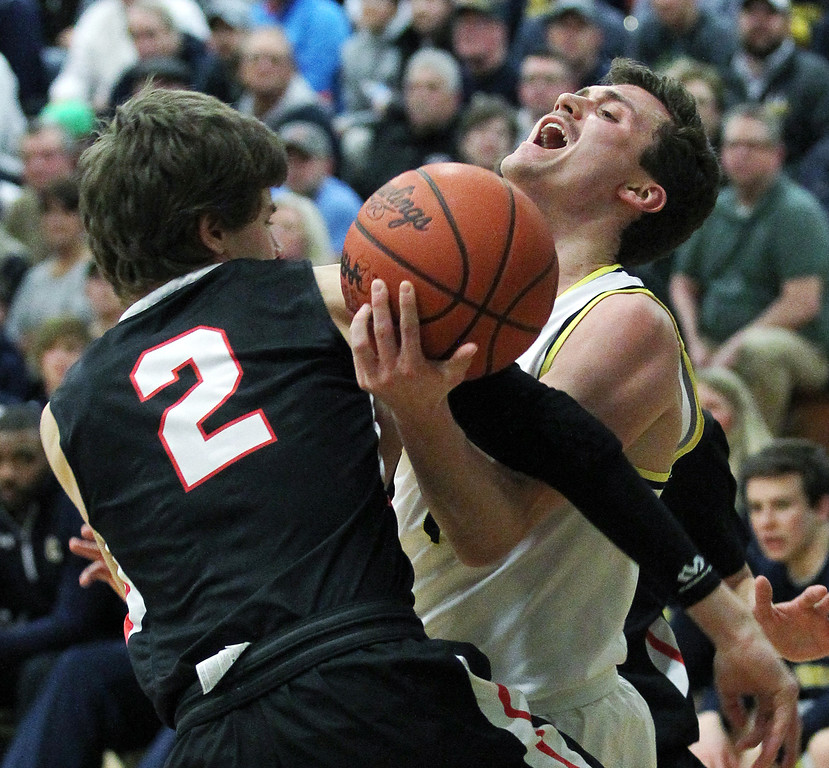 . Foster Loyer, Clarkston, takes a hard foul going to the basket from Matt Johansson (2), Troy, during regional semifinal basketball action at West Bloomfield High School Monday, March 12, 2018. The Wolves took an early lead and never looked back downing Troy 71-46. (For The Oakland Press / LARRY McKEE)