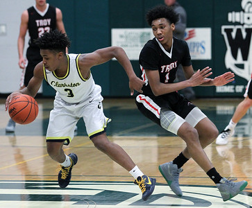 C.J. Robinson (3), Clarkston, slips past defender Leon Ayers, Troy, during regional semifinal basketball action at West Bloomfield High School Monday, March 12, 2018. Clarkston defeated Troy 71-46. (For The Oakland Press / LARRY McKEE)