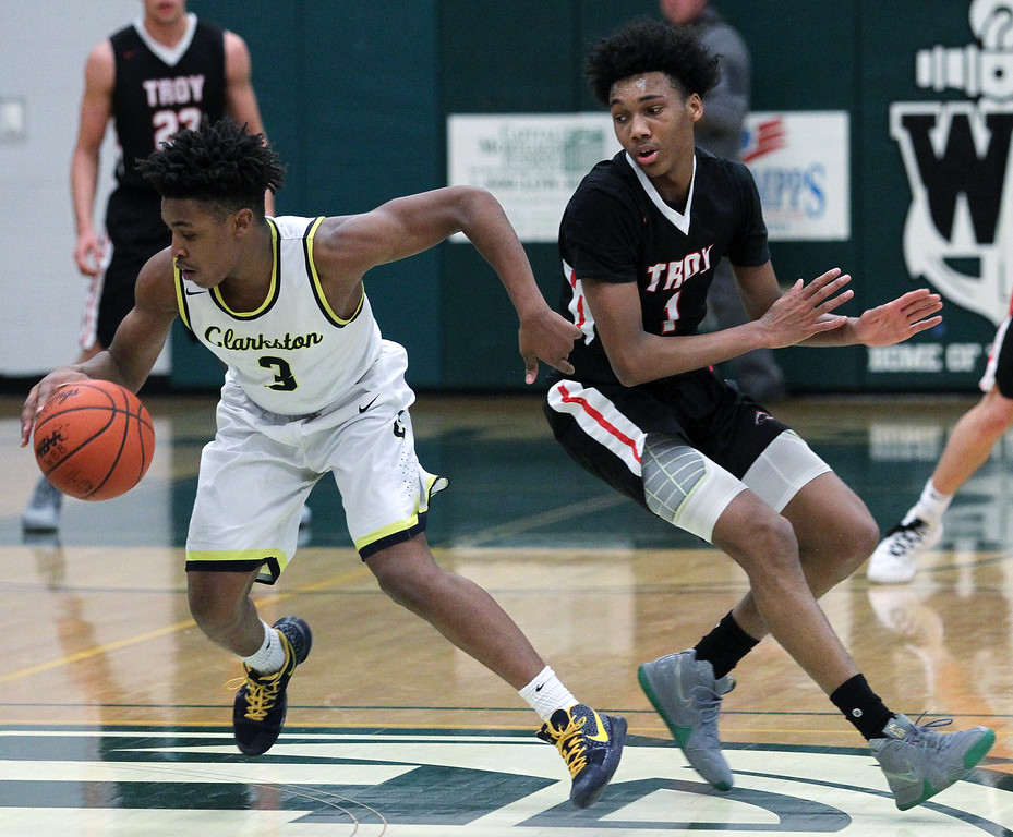 . C.J. Robinson (3), Clarkston, slips past defender Leon Ayers, Troy, during regional semifinal basketball action at West Bloomfield High School Monday, March 12, 2018. Clarkston defeated Troy 71-46. (For The Oakland Press / LARRY McKEE)
