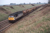 10 April 1992 :: 56033 now with Construction sub-sector colours is hauling an empty stone train at Uffington