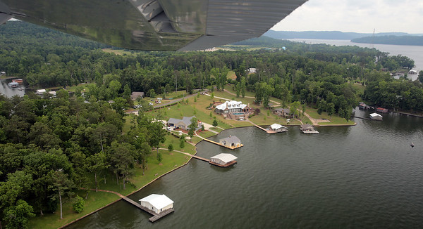 Homes and boathouses along the shore of Lake Guntersville as seen from Michael Kirkpatrick's seaplane. The lake is located in north Alabama, between Bridgeport and Guntersville. Created by Guntersville Dam along the Tennessee River, it stretches 75 miles from Guntersville Dam to Nickajack Dam. It is Alabama's largest lake at 69,000 acres. Overall, only 20% of the shoreline can be developed, leaving the shores of the constant-level lake mostly green.
