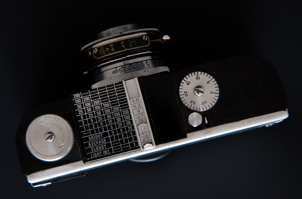 """My copy is a bit of an anomaly.  It is clearly marked """"A2F"""" inside the body.  However, on this example the exposure calculator on top of the camera is painted black with chrome numbers in a style that is typical of the post-war Argus A2B.  The A2F was manufactured with a removable plunger button for the shutter, this copy has a regular trigger button, as seen on the original Argus A.  Since there were so many different models in the A series, it's possible this model could have had parts replaced from other cameras in the series, or maybe it was manufactured using left-over parts in the Argus factory."""