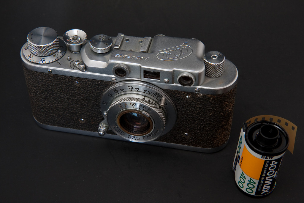 Pictured here with the lens collapsed into the body and a roll of film for scale.  This is one of my most pocket-able cameras due to it's small size.