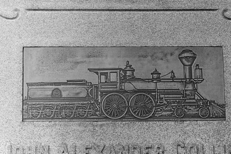 According to Woodlawn's website John Alexander Collins' grave marker is the tallest in the cemetery.  It includes this copper inlay of a locamotive.  Collins started up the C H and D railroad in the mid 1800's.