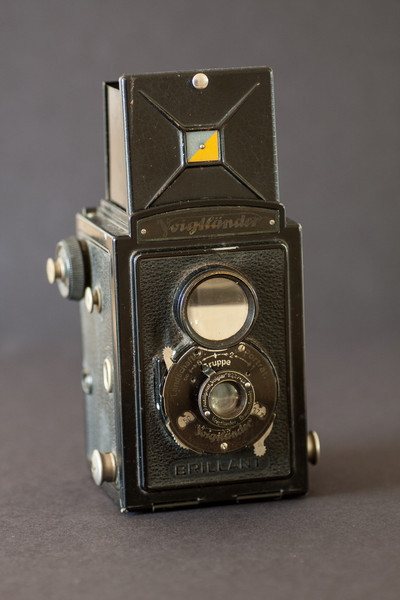 "The Voigtlander Brillant was a low cost German TLR that was intended for photographers on a budget (yes, ""Brillant"" is the correct spelling).  This is an example of the early metal bodied, zone focusing version of the Brillant which was introduced in 1932.  It's a simple camera but it does have more than one shutter speed and a choice of aperture settings.  As implied by the name, the viewfinder is very bright.  Unfortunately this is one of the few cameras in my collection that is not working."