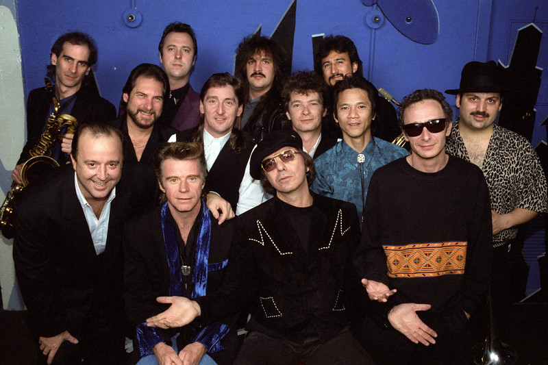 """Dave Emunds R&R Revue posing backstage at the Warfield Theater in San Francisco on April 7, 1990. Front row, (l-r): Kim Wilson, Dave Edmunds, Dion DiMucci, Graham Parker. Second row, (l-r): Steve Cropper, Terry Williams, Dave Charles, Phil Chen, Richie """"La Bamba"""" Rosenberg."""