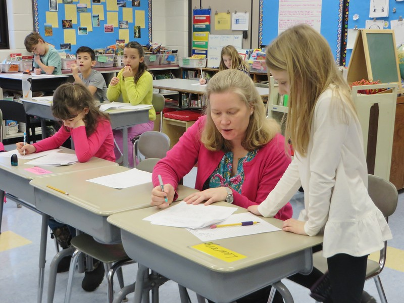 Morris Elementary School third-grade teacher Sarah Gerney helps her students through a writing assignment.