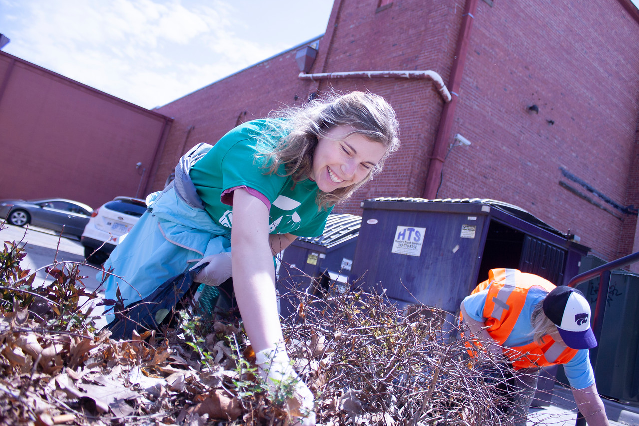 Emma Pettay, freshman in biology and member of Students for Environmental Action at K-State, picks trash out of bushes as part of Clean Up MHK on Sunday, April 22, 2018, near Aggieville. (Tiffany Roney | Collegian Media Group)