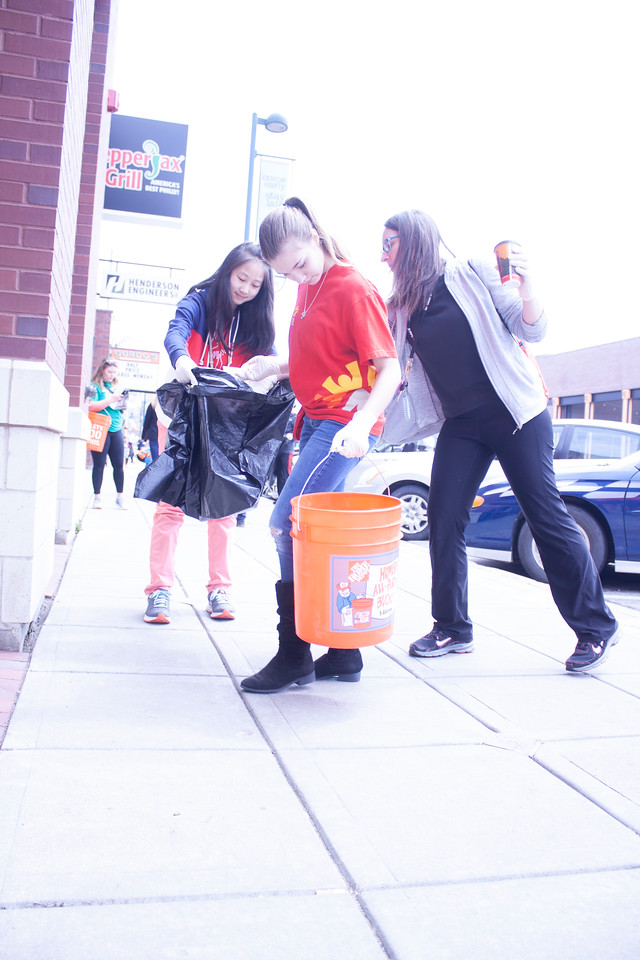 Athena Sargent (front) and Selena Wang, eighth grader at Anthony Middle School, and Paula Dover, coordinator of Youth Volunteer Corps, volunteer at Clean Up MHK in Aggieville on Sunday, April 22, 2018. (Tiffany Roney | Collegian Media Group)
